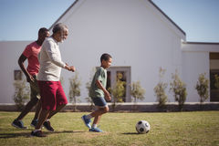 Boy playing football with his father and grandson. In garden Royalty Free Stock Photo