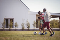 Boy playing football with his father and grandson. In garden Royalty Free Stock Images