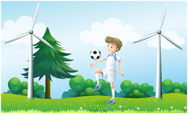 A boy playing football near the windmills Royalty Free Stock Images