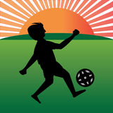 Boy playing football in playfield Royalty Free Stock Image