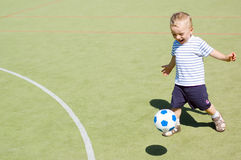 Boy playing football stadium. Almost 2 years old (23 months) boy playing football on stadium Royalty Free Stock Images