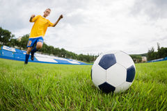 Boy playing football at the stadium. Royalty Free Stock Photo