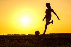 Boy playing football, teen exercising in nature at sunset
