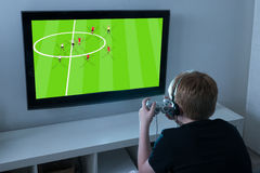 Boy Playing Football Videogame On Television. Boy With Joystick Playing Football Videogame On Television At Home Stock Photos