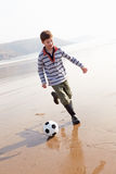 Boy Playing Football On Winter Beach Stock Images