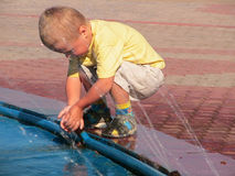 Boy playing with fountain. Young boy playing with jets of water in fountain outdoors stock photos