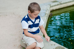 Boy playing by the fountain Royalty Free Stock Photography