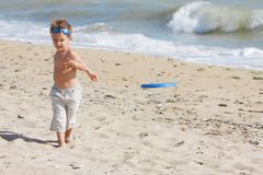 Boy playing frisbee on beach. Young boy playing frisbee on beach Royalty Free Stock Photography