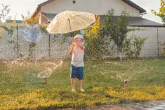 Summer activities. Children playing outdoor. Happy boy playing outdoor with watering system. Summer vacation. Summer royalty free stock photography