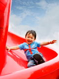 Boy playing in funfair. Picture of a little chinese boy sliding down happily in a funfair royalty free stock photos