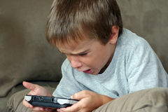 Boy Playing Game. Boy playing a hand held game Royalty Free Stock Photos