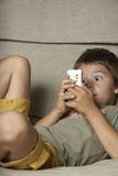 Boy Playing Game on Cell Phone. A young boy sits on the couch and plays a cell phone game with an intense expression on his face. Vertical shot Stock Images