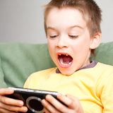 Boy playing game console Stock Photos