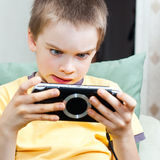 Boy playing game console. Young boy playing handheld game console Royalty Free Stock Images