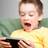 Boy playing game console. Young boy playing handheld game console Stock Photos