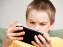 Boy playing game console Stock Photography