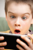 Boy playing game console. Young boy playing handheld game console Stock Image