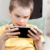 Boy playing game console. Young boy playing handheld game console Royalty Free Stock Image