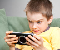 Boy playing game console. Young boy playing handheld game console Royalty Free Stock Photo