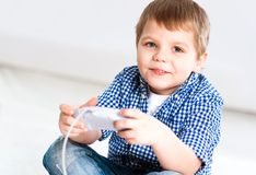 Boy playing on a game console Stock Images