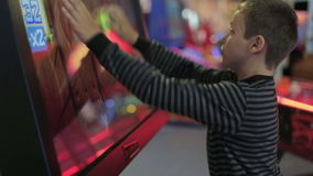 A boy playing a game on the game simulator. A boy playing a game on the gaming machine stock video footage
