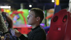 A boy playing a game on the game simulator. A boy playing a game on the gaming machine stock footage