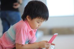 Boy playing game. Little boy playing game on mobile royalty free stock photography