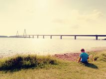 Boy is playing game on offshore, view to the big traffic bridge over bay . The two road bridge with high towers royalty free stock photos