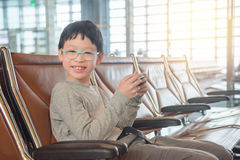 Boy playing game on smart phone at airport Stock Photography