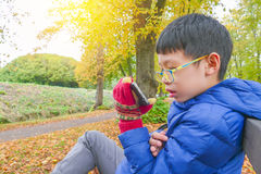 Boy playing game on smart phone in park Stock Images