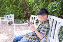 Boy playing game on smart phone Royalty Free Stock Photos