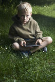 Boy playing game with tablet pc outdoors. Child Boy with tablet pc outdoors, sitting on grass lawn Royalty Free Stock Images
