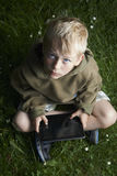 Boy playing game with tablet pc outdoors. Child Boy with tablet pc outdoors, sitting on grass lawn Stock Photography