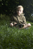 Boy playing game with tablet pc outdoors. Child Boy with tablet pc outdoors, sitting on grass lawn Stock Images