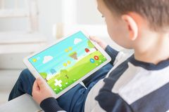 Boy playing game on white tablet. Home interior in bacgkround. stock photography