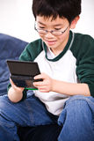 Boy playing games. A shot of an asian boy playing electronic games Royalty Free Stock Image