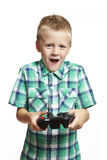 Boy playing games console. 8 year old boy playing games console holding controller on white background Royalty Free Stock Images