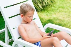 Free Boy Playing Games On The Telephone. Gadget Dependency Disorder Problem For Kids During Holiday Vacation At The Seaside Royalty Free Stock Photo - 194152375
