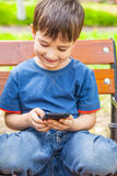 Boy playing games on smartphone Stock Photography