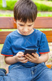 Boy playing games on smartphone Stock Photo