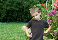 Boy playing in garden. Half body portrait of boy with funny expression playing in garden, flowers in background Royalty Free Stock Images