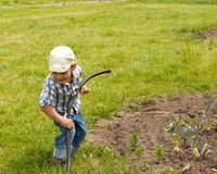 Boy playing with garden hose Stock Photos