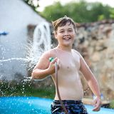Boy playing with garden hose Royalty Free Stock Photo