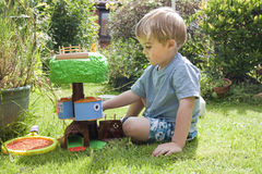 BOY PLAYING IN THE GARDEN WITH TOY Stock Photography