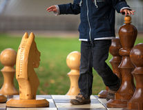 Boy is playing with giant chess Royalty Free Stock Image