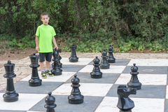 Boy playing giant outdoor chess Stock Image