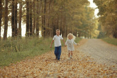 Boy playing with a girl in  autumn road Royalty Free Stock Photography