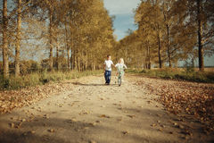 Boy playing with a girl in the autumn  road Royalty Free Stock Photo