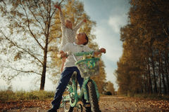 Boy playing with a girl in the autumn  road Stock Photos