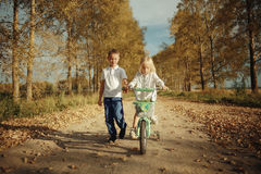 Boy playing with a girl in country road Royalty Free Stock Photos